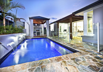 63767867 - modern swimming pool side with glass cover at night with dark blue water with a tiled poolside under the sky at evening