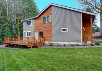 Charming newly renovated home exterior, natural wood siding and grey siding create a beautiful curb appeal. View of a nice walk out deck with wooden handrails.