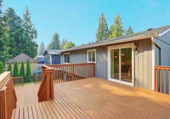 Empty upper level deck boasts redwood railings overlooking the lower level deck.